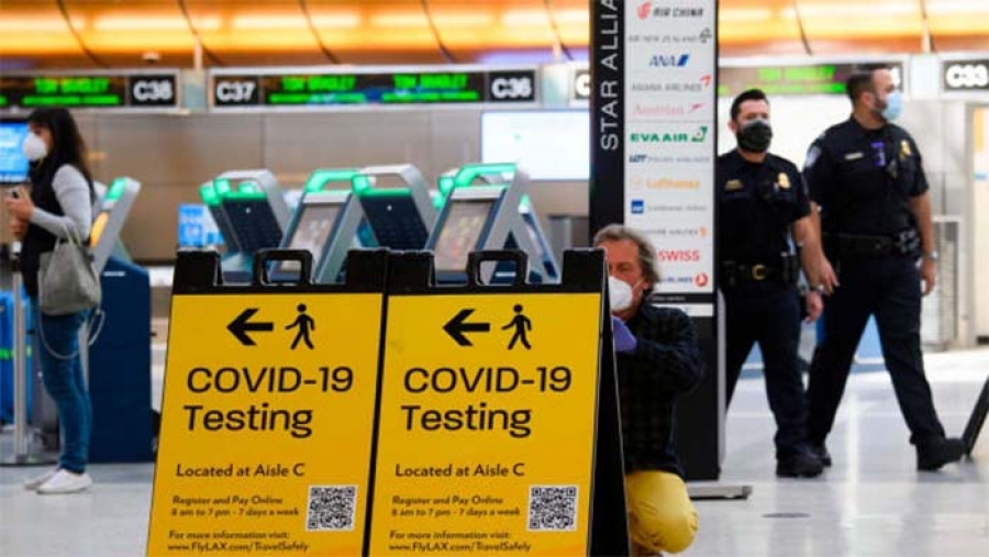 A traveler takes a photo of a Covid-19 testing sign at Los Angeles International Airport (LAX) in February 2021.  |