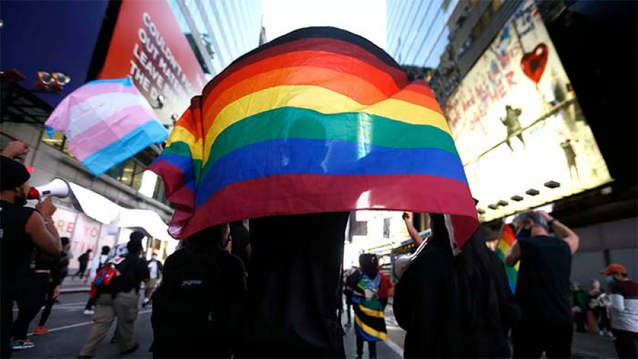 A protester holds a rainbow flag in Times Square in Oct. 2020.  |